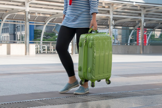 Il giovane adolescente sta portando il bagaglio all'aeroporto Foto Premium