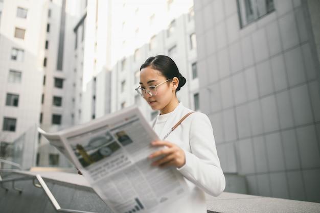 Il giovane banchiere o ragioniere femminile asiatico attraente in vetri sta leggendo il giornale fuori di un centro di ufficio moderno Foto Premium