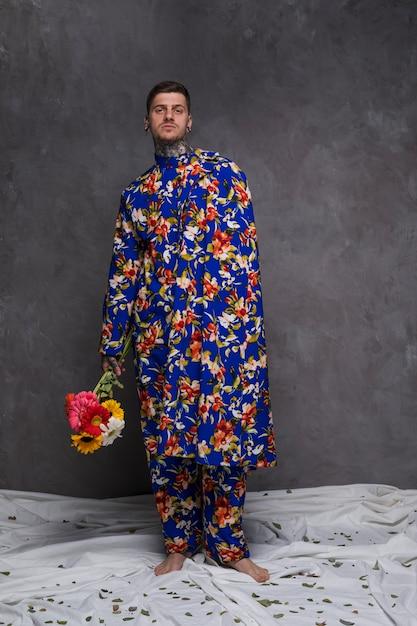 Il giovane bello in vestiti floreali che tengono la gerbera fiorisce a disposizione contro la parete grigia Foto Gratuite