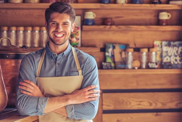 Il giovane cameriere bello in grembiule sta esaminando la macchina fotografica. Foto Premium