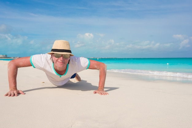 Il giovane che fa i push up sulla spiaggia perfetta Foto Premium