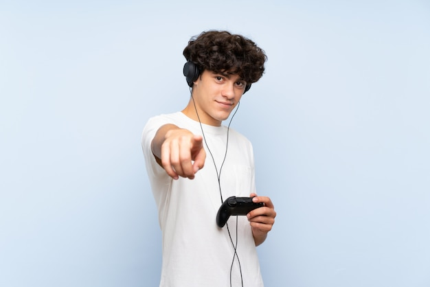 Il giovane che gioca con un regolatore del videogioco sopra la parete blu isolata indica il dito voi con un'espressione sicura Foto Premium