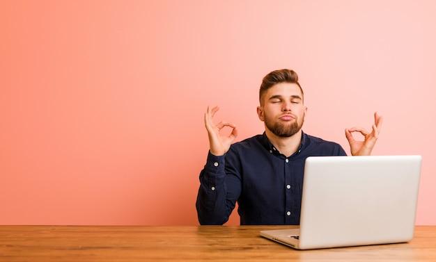 Il giovane che lavora con il suo laptop si rilassa dopo la giornata lavorativa dura, sta eseguendo lo yoga. Foto Premium