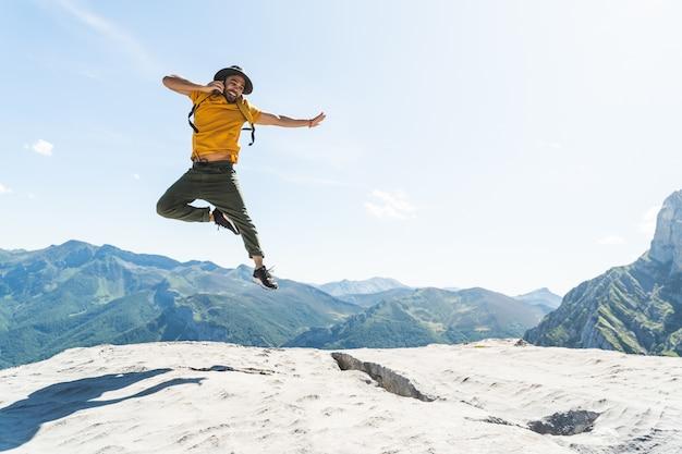 Il giovane che salta avendo una telefonata sopra una montagna che indossa uno zaino giallo. Foto Premium