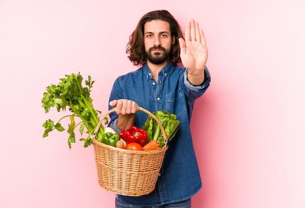 Il giovane che seleziona le verdure organiche dal suo giardino ha isolato la condizione con la mano tesa che mostra il fanale di arresto, impedendovi. Foto Premium