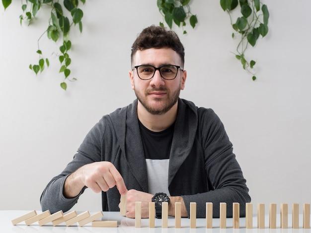 Il giovane che si siede in occhiali guarda la giacca grigia che gioca con le piccole figure di legno con la pianta su bianco Foto Gratuite