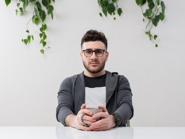 Il giovane che si siede in occhiali guarda la giacca grigia con la pianta su bianco Foto Gratuite