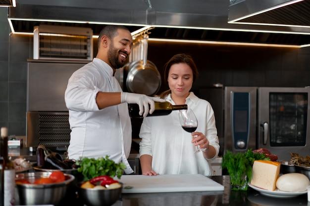 Il giovane chef africano sta cucinando insieme alla ragazza caucasica in cucina Foto Premium