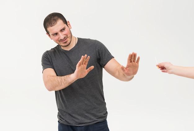 Il giovane dice no alla sigaretta offerta da una persona isolata su priorità bassa bianca Foto Gratuite