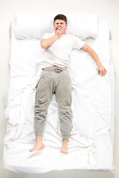 Il giovane disteso su un letto Foto Gratuite
