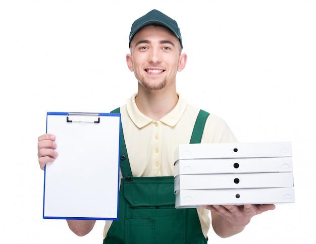 Il giovane fattorino sorridente sta tenendo le scatole di una pizza. Foto Premium