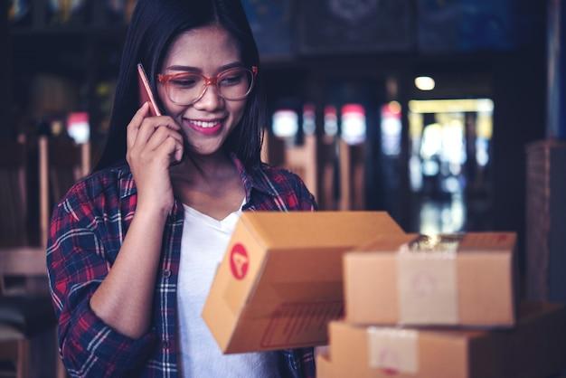 Il giovane imprenditore, proprietario di affari dell'adolescente lavora a casa, scatola per la consegna Foto Premium