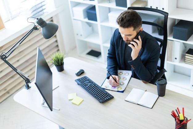 Il giovane lavora in ufficio alla scrivania di un computer con documenti, schemi e telefono. Foto Premium