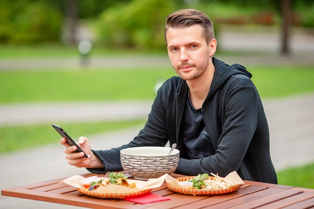 Il giovane mangiatore di uomini porta via le tagliatelle sulla via Foto Premium