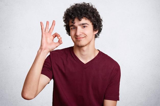 Il giovane maschio bello con capelli ricci, fa il segno ...