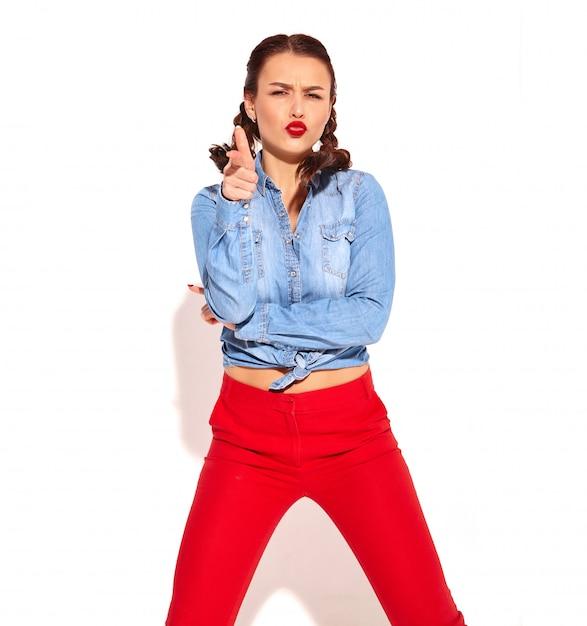 Il giovane modello sorridente felice della donna con trucco luminoso e le labbra rosse con due trecce in blue jeans dell'estate copre isolato. imitando la pistola per mano e sparando Foto Gratuite