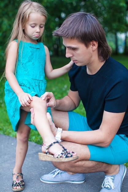Il giovane padre compatisce la sua piccola figlia, che le ha fatto male alla gamba Foto Premium