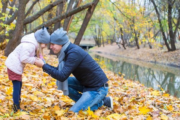 Il giovane padre si diverte con la figlia sveglia nel parco di autunno Foto Premium
