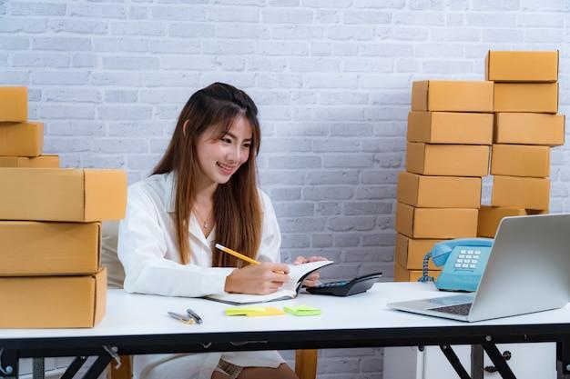 Il giovane proprietario dell'imprenditore di affari scrive nella consegna in taccuino sull'affare di consegna in linea Foto Premium