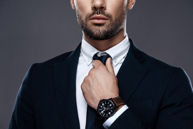 Il giovane raddrizza la cravatta, il viso con la barba lunga. Foto Premium