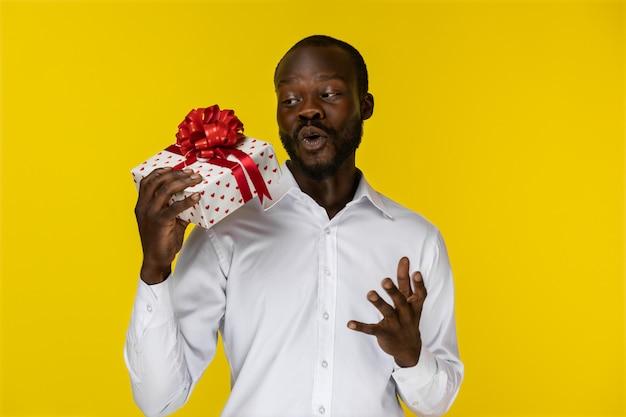 Il giovane ragazzo afroamericano barbuto emozionante sta tenendo un regalo in una mano Foto Gratuite