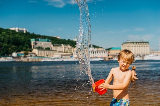 Il giovane ragazzo con gli occhi chiusi rovescia l'acqua sulla spiaggia del mare Foto Gratuite