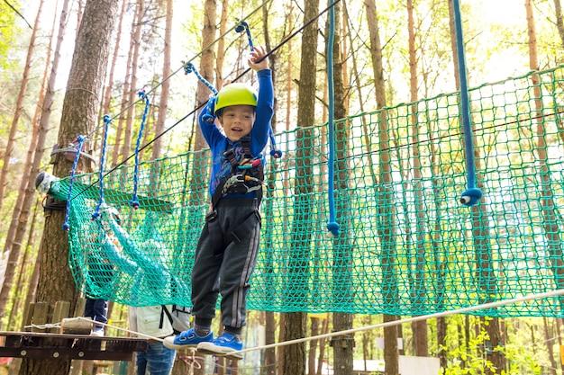 Il giovane ragazzo in casco cammina dalla corda Foto Premium
