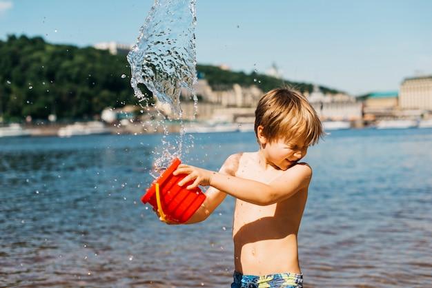 Il giovane ragazzo versa l'acqua dal secchio sulla spiaggia del mare Foto Gratuite
