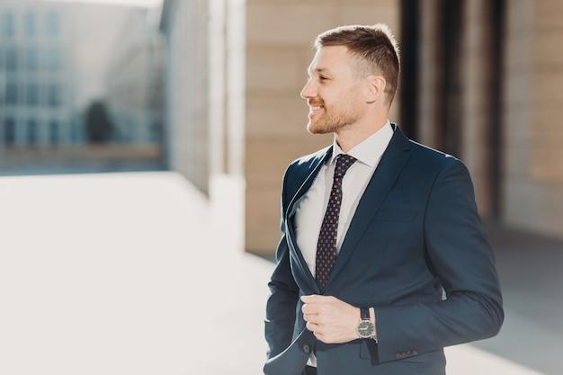 Il giovane responsabile maschio non rasato prospero positivo indossa i vestiti convenzionali Foto Premium