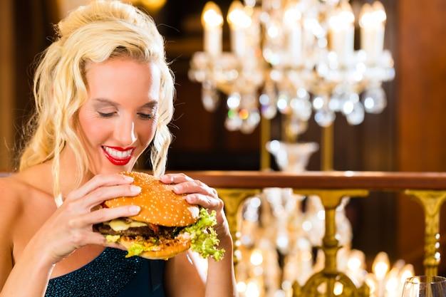 Il giovane ristorante di cucina raffinata mangia un hamburger, si comporta in modo improprio Foto Premium