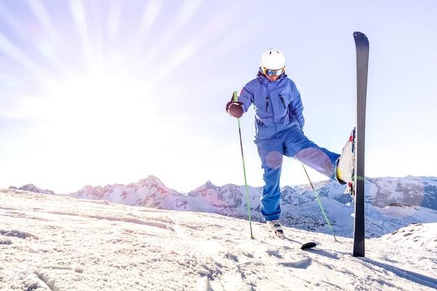 Il giovane sciatore sull'uniforme blu al tramonto sopra si rilassa il momento nella stazione sciistica francese delle alpi Foto Premium