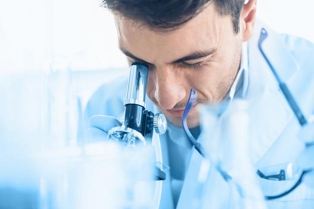 Il giovane scienziato guarda attraverso il microscopio mentre fa la ricerca in laboratorio scientifico Foto Premium