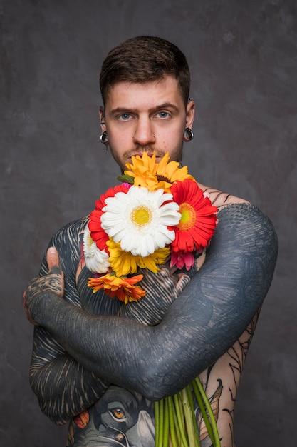 Il giovane senza camicia con tatuato sul suo corpo che tiene la bella gerbera fiorisce a disposizione che sta contro il fondo grigio Foto Gratuite