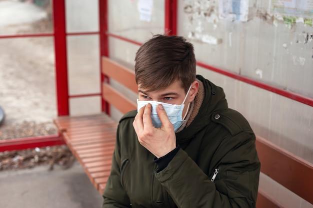 Il giovane si siede alla stazione degli autobus in primo piano monouso maschera medica. Foto Premium