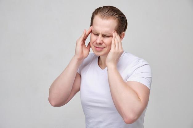 Il giovane si tocca la testa con le mani e si acciglia fortemente con un mal di testa. Foto Premium
