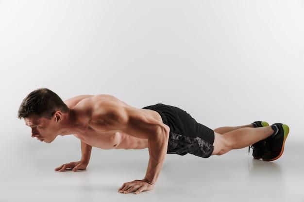 Il giovane sportivo concentrato fa gli esercizi di sport Foto Gratuite