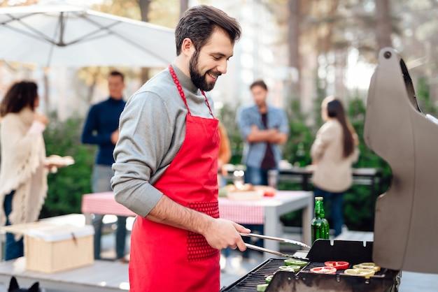 Il giovane sta cucinando il cibo del barbecue. Foto Premium