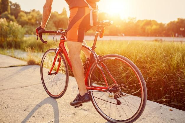 Il giovane sta pedalando in bici da strada la sera Foto Gratuite