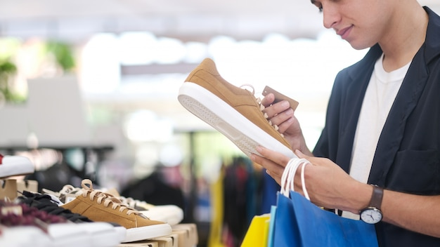 Il giovane sta scegliendo la scarpa mentre faceva la spesa al centro commerciale. Foto Premium
