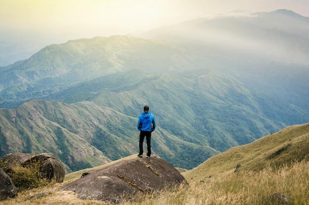 Il giovane turista dell'asia alla montagna sta guardando sopra l'alba nebbiosa e nebbiosa del mattino Foto Premium