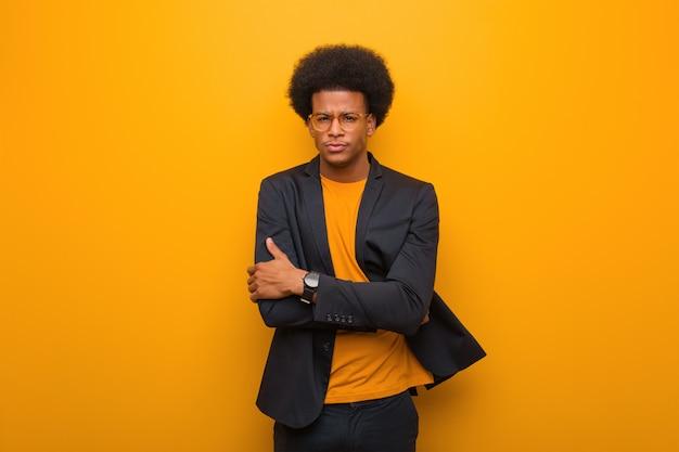 Il giovane uomo afroamericano di affari sopra un incrocio arancio della parete arma rilassato Foto Premium