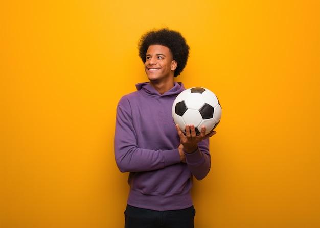Il giovane uomo afroamericano di sport che tiene un pallone da calcio che sorride sicuro e che attraversa le armi, cercante Foto Premium