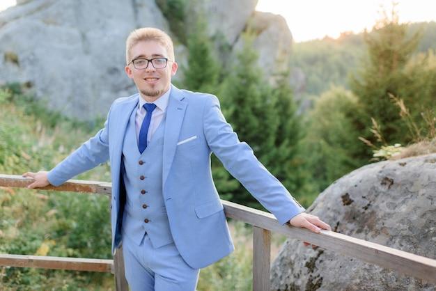Il giovane uomo alla moda sorriso vestito in vestito e gli occhiali alla moda blu sta stando vicino alle rocce enormi Foto Gratuite