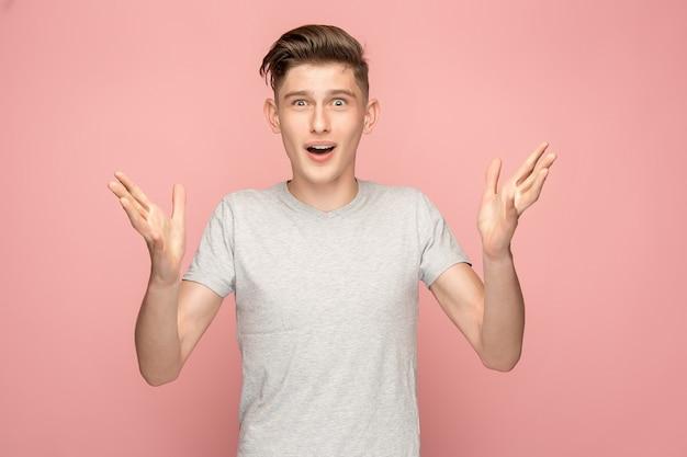 Il giovane uomo attraente che sembra sorpreso isolato sul rosa Foto Gratuite