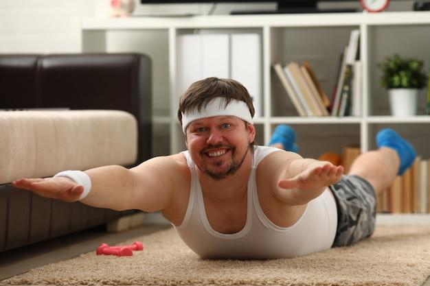 Il giovane uomo attraente di forma fisica si trova su una stuoia grassa con Foto Premium