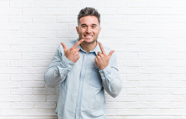 Il giovane uomo bello contro una parete di mattoni sorride, indicando le dita alla bocca. Foto Premium