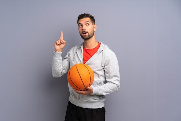 Il giovane uomo bello del giocatore di pallacanestro che intende realizzare la soluzione mentre solleva un dito su Foto Premium