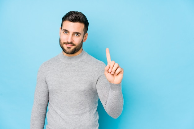 Il giovane uomo caucasico contro una parete blu ha isolato la mostra del numero uno con il dito. Foto Premium