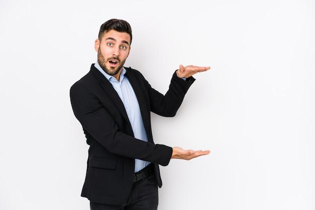 Il giovane uomo caucasico di affari contro una parete bianca ha isolato colpito e stupito tenendo uno spazio della copia fra le mani. Foto Premium