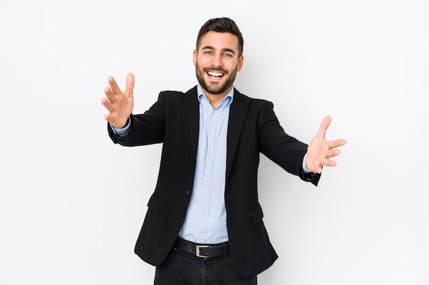 Il giovane uomo caucasico di affari contro una priorità bassa bianca isolata si sente sicuro dare un abbraccio alla macchina fotografica. Foto Premium